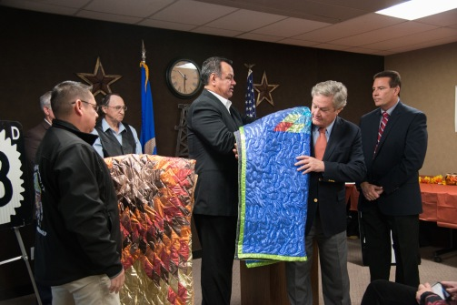 Gov. Jack Dalrymple & NDDOT Director Grant Levi are presented with blankets by Tribal Councilman Ken Hall at an event to commemorate the completion of the $20 million New Town Main Street reconstruction project